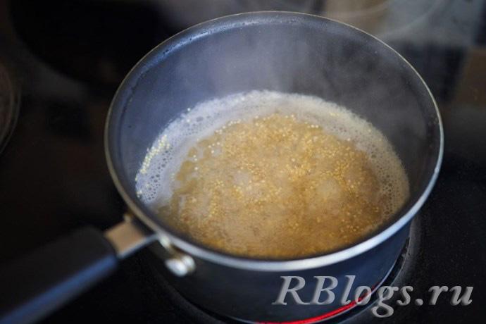 Каша из семян амаранта варится на плите в кастрюле без крышки.